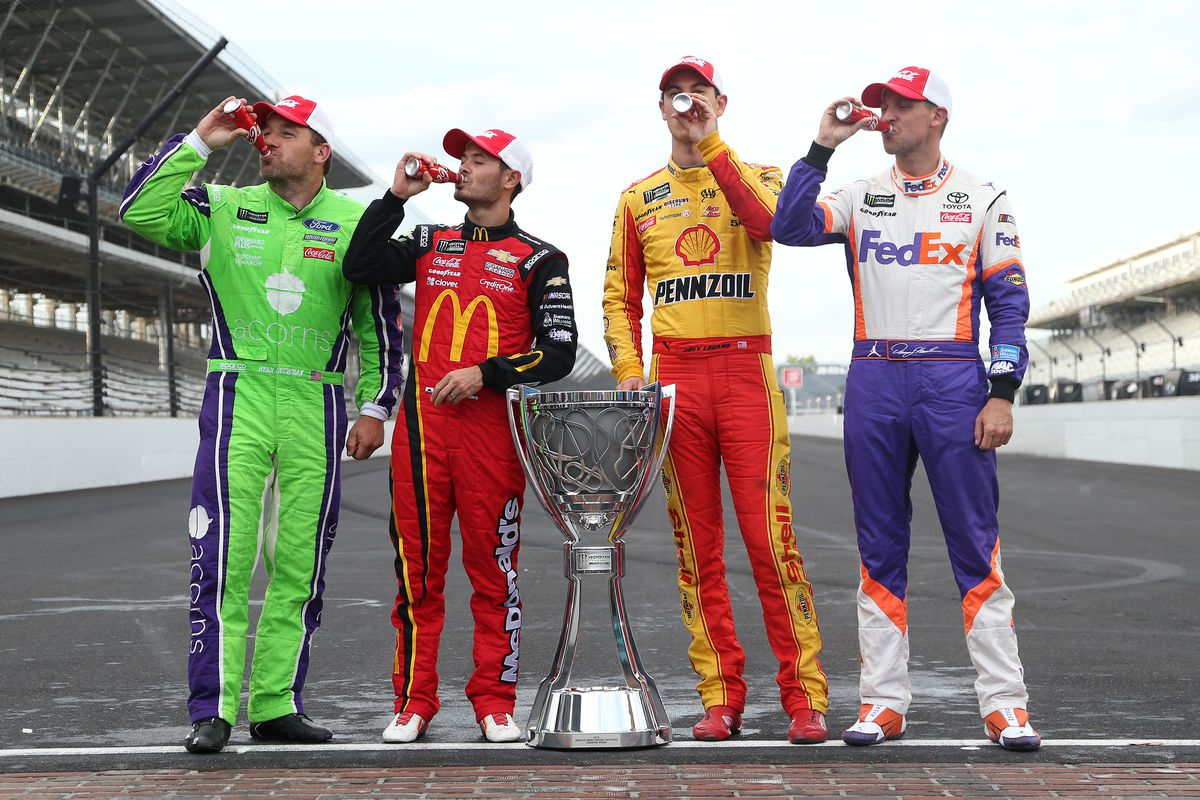 Ryan Newman, Kyle Larson, Joey Logano, and Denny Hamlin, driver of the #11 FedEx Express Toyota, pose for a photo with the Monster Energy NASCAR Cup Series trophy to start the playoffs following the Monster Energy NASCAR Cup Series Big Machine Vodka 400 at the Brickyard at Indianapolis Motor Speedway on September 08, 2019 in Indianapolis, Indiana.