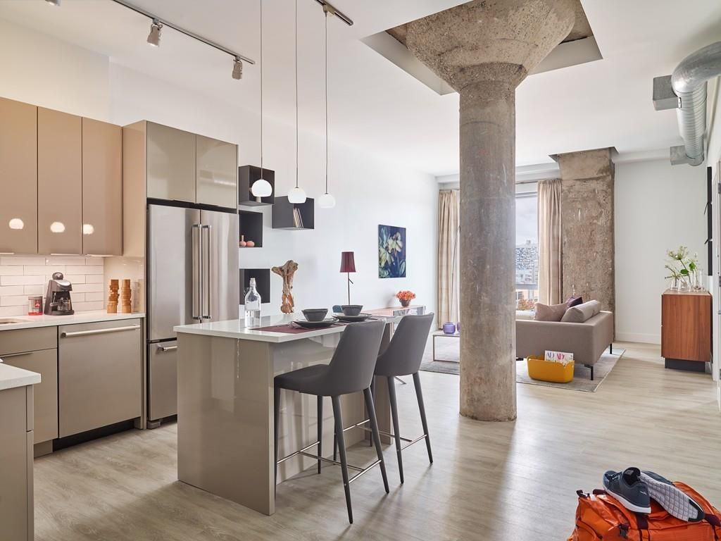 An open living room-kitchen with a large column in the midst of its and an island in the kitchen area.