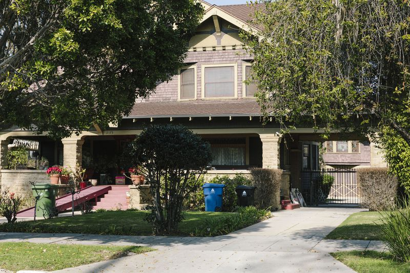 A large old home painted brown and cream with a red front porch is fronted by a grass lawn and leafy trees.