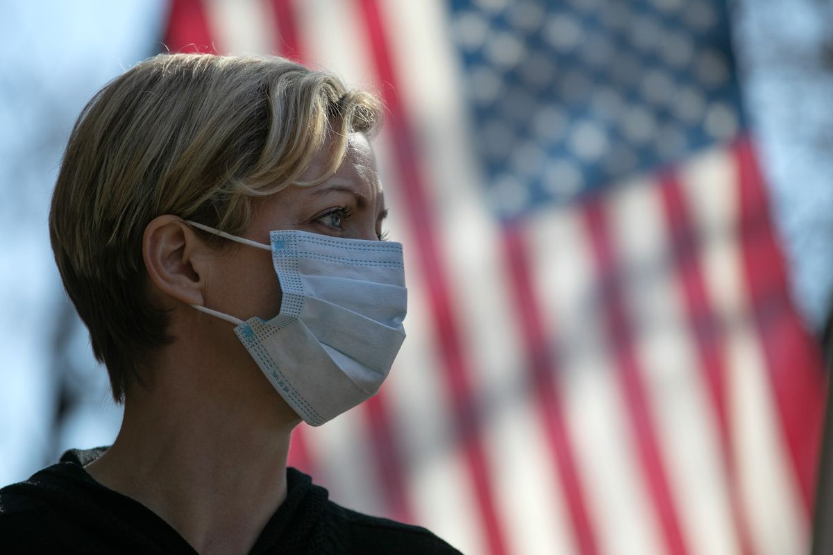 The profile of a person wearing a face mask, with an American flag in the background.