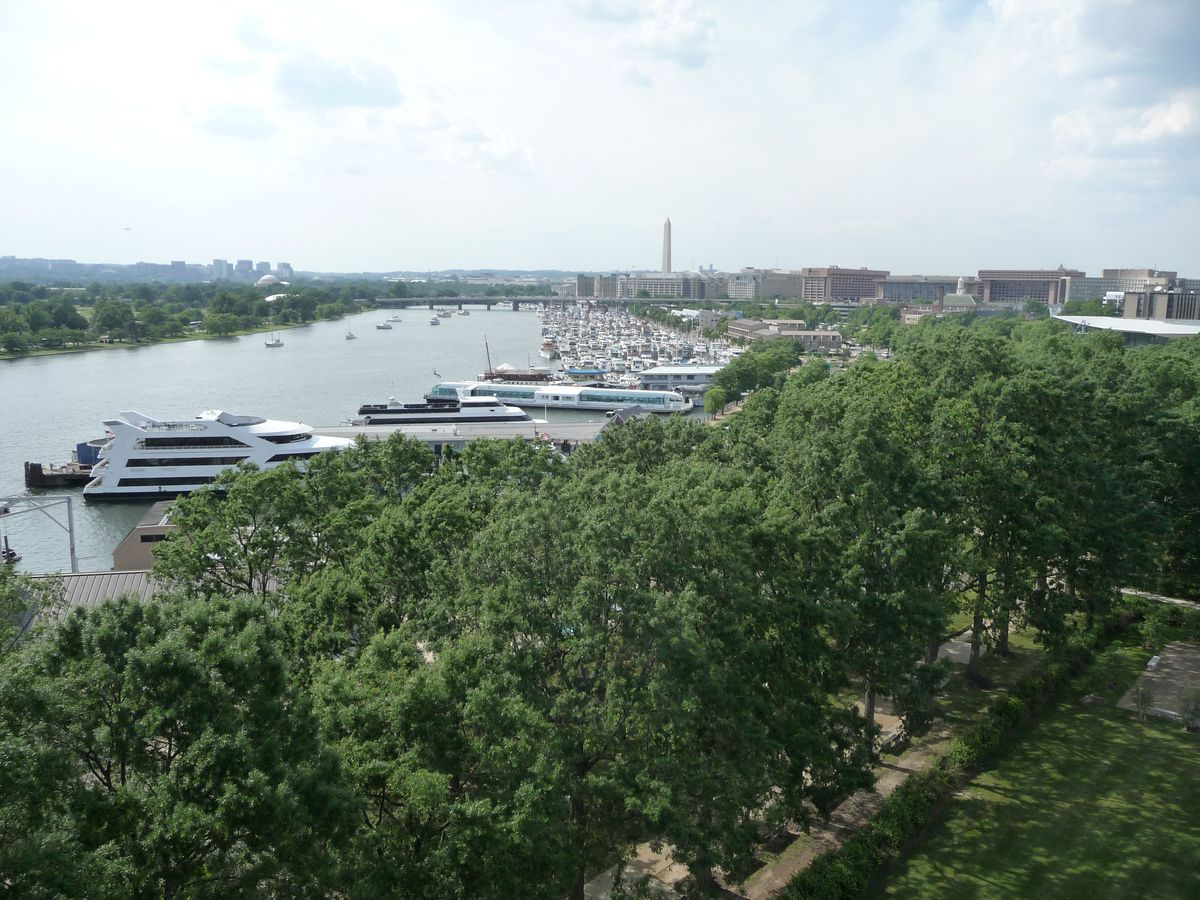 In the foreground are trees and a lawn. In the distance is a body of water and a boat marina.