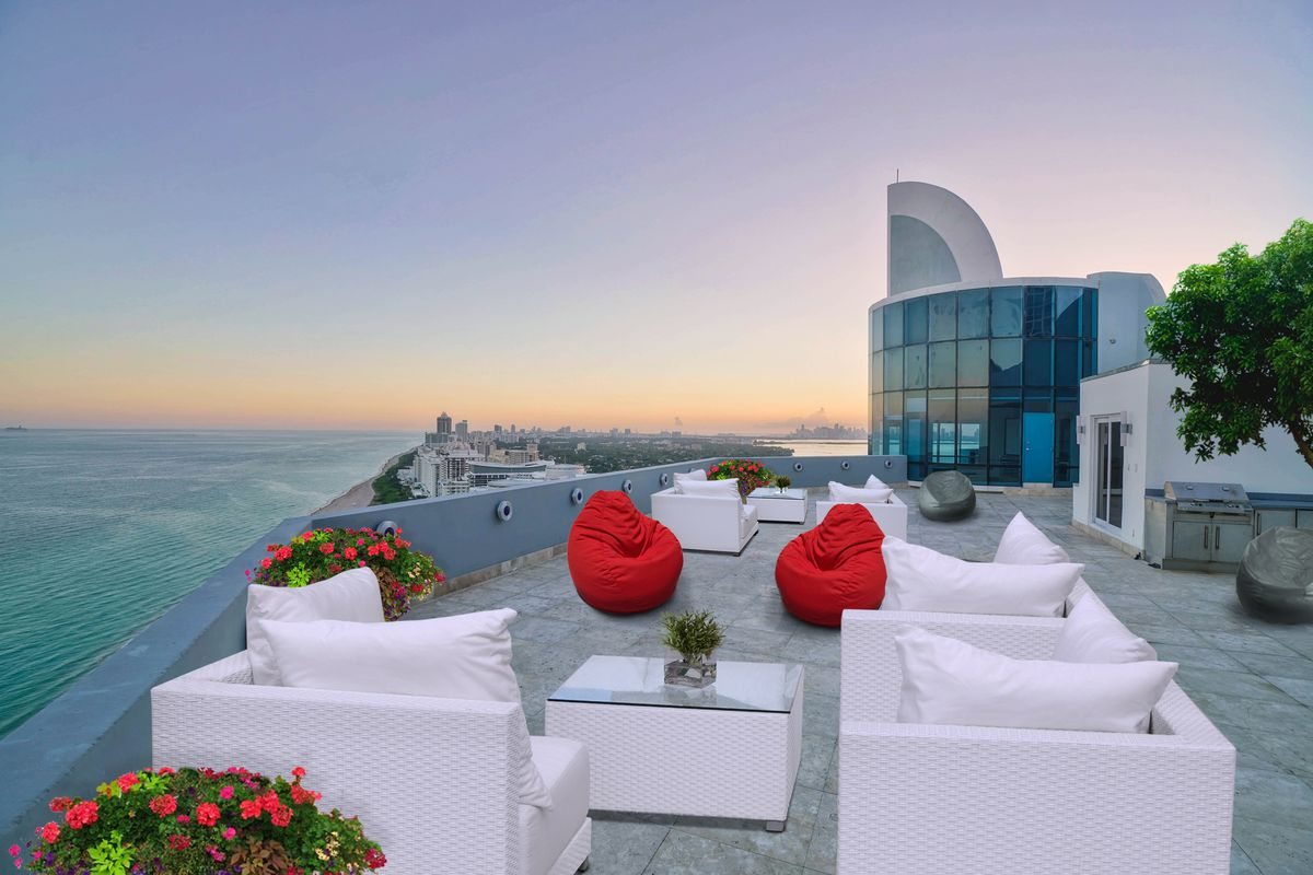 View of a huge rooftop deck with white furniture with an ocean view of Miami Beach in the back left.
