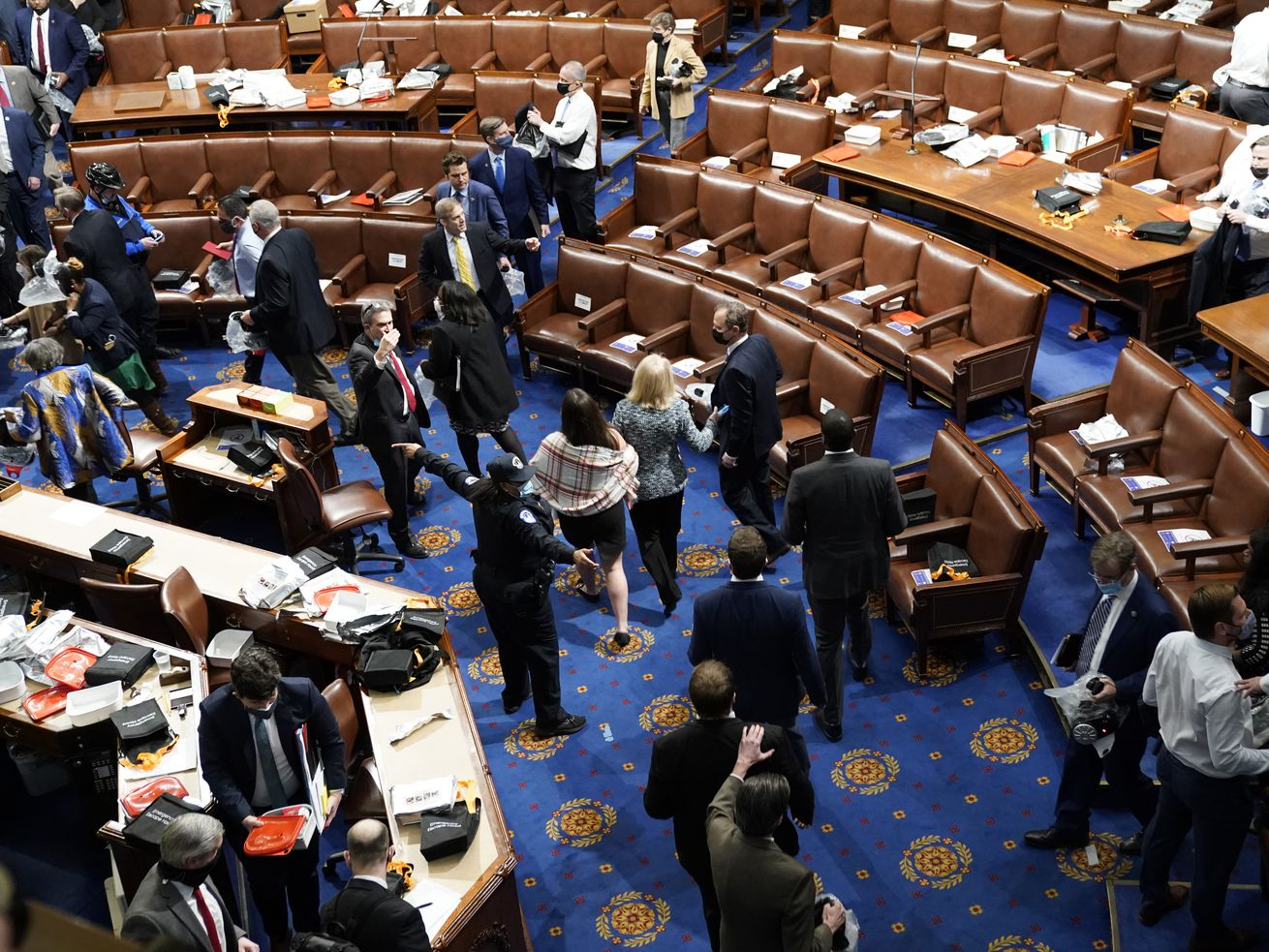 An aerial view of the chamber shows papers strewn across brown leather chairs as lawmakers in suits and formal dresses scramble down aisles and cluster in confusion in front of the speaker's dais.