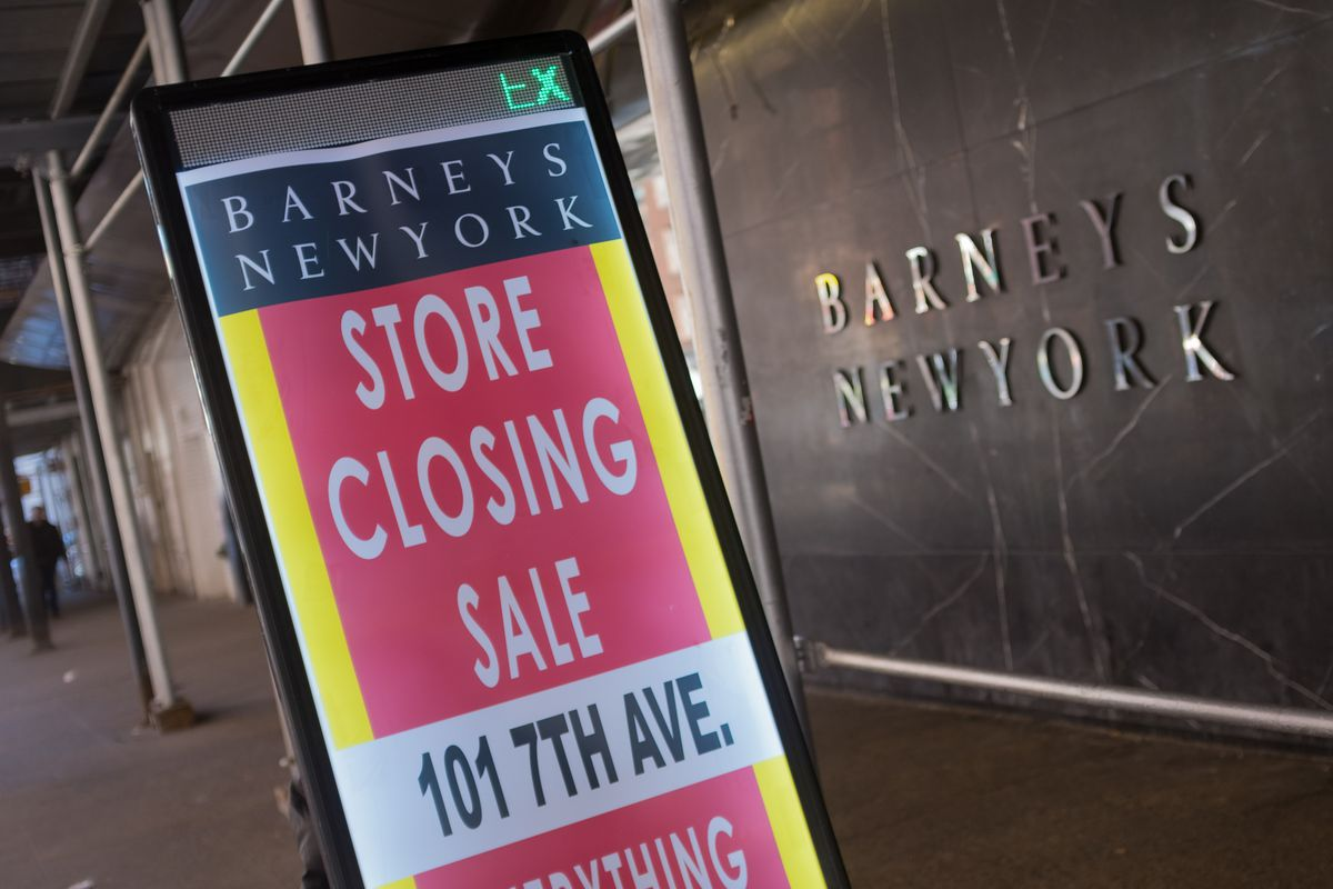 """A sign outside Barneys New York department store reads, """"Barneys New York store closing sale, 101 7th Ave."""""""