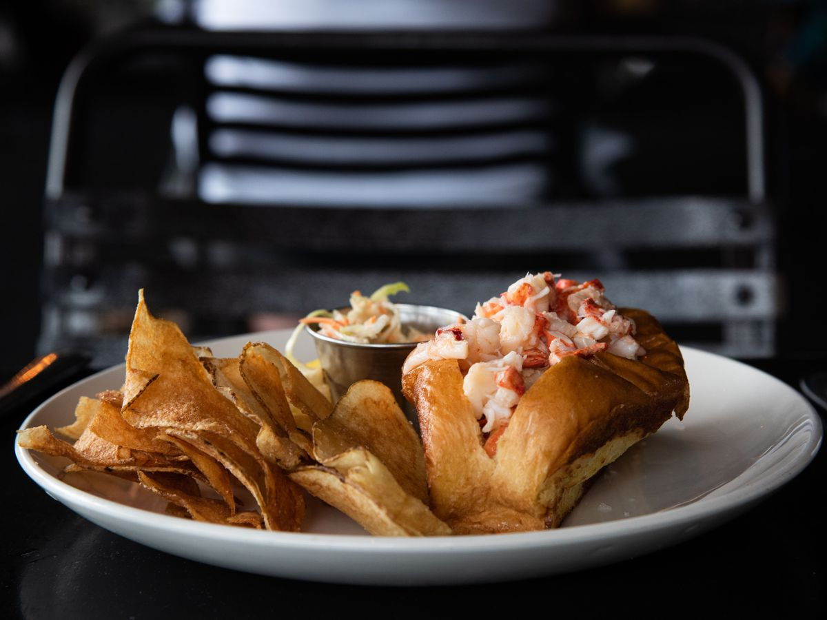 A lobster roll with a side of chips sits on a white plate on a black table
