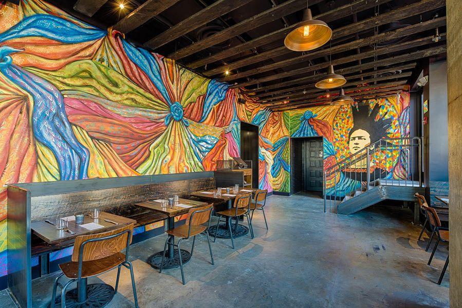 Brightly colored murals in a dining room at Espita Mezcaleria