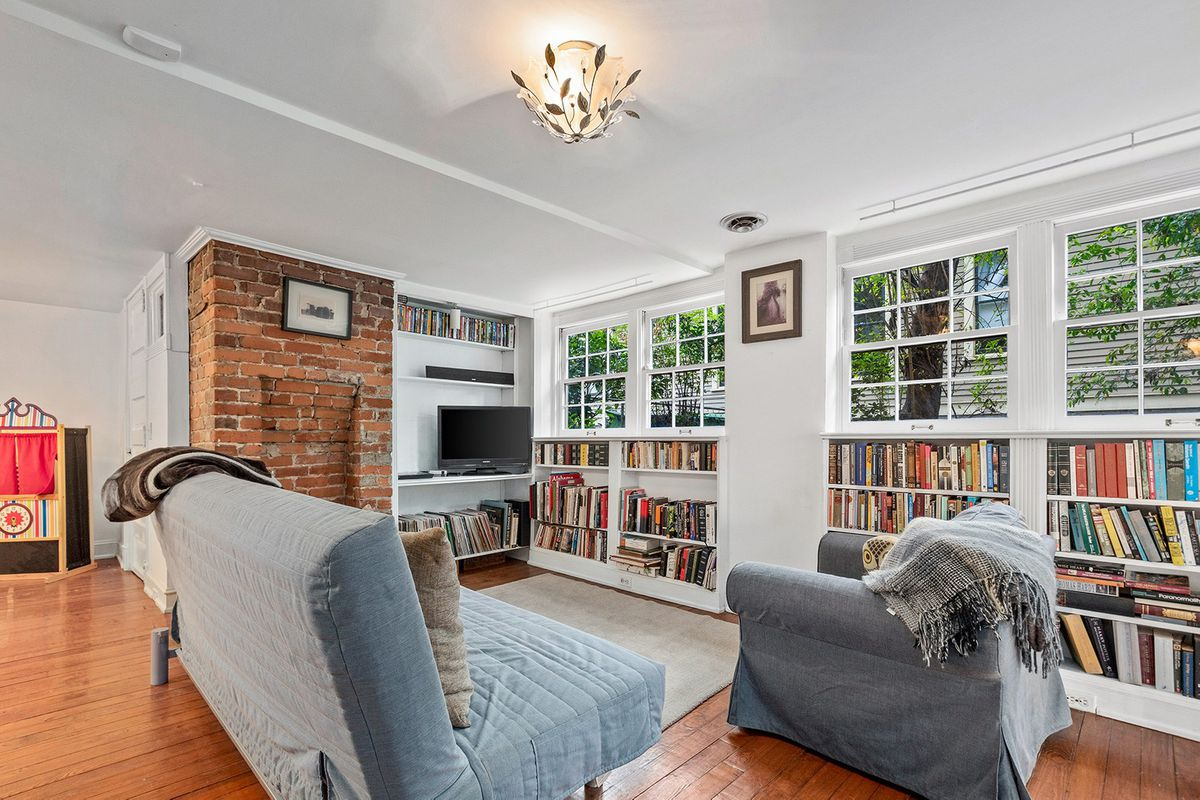 A basement living room with many books on the walls.