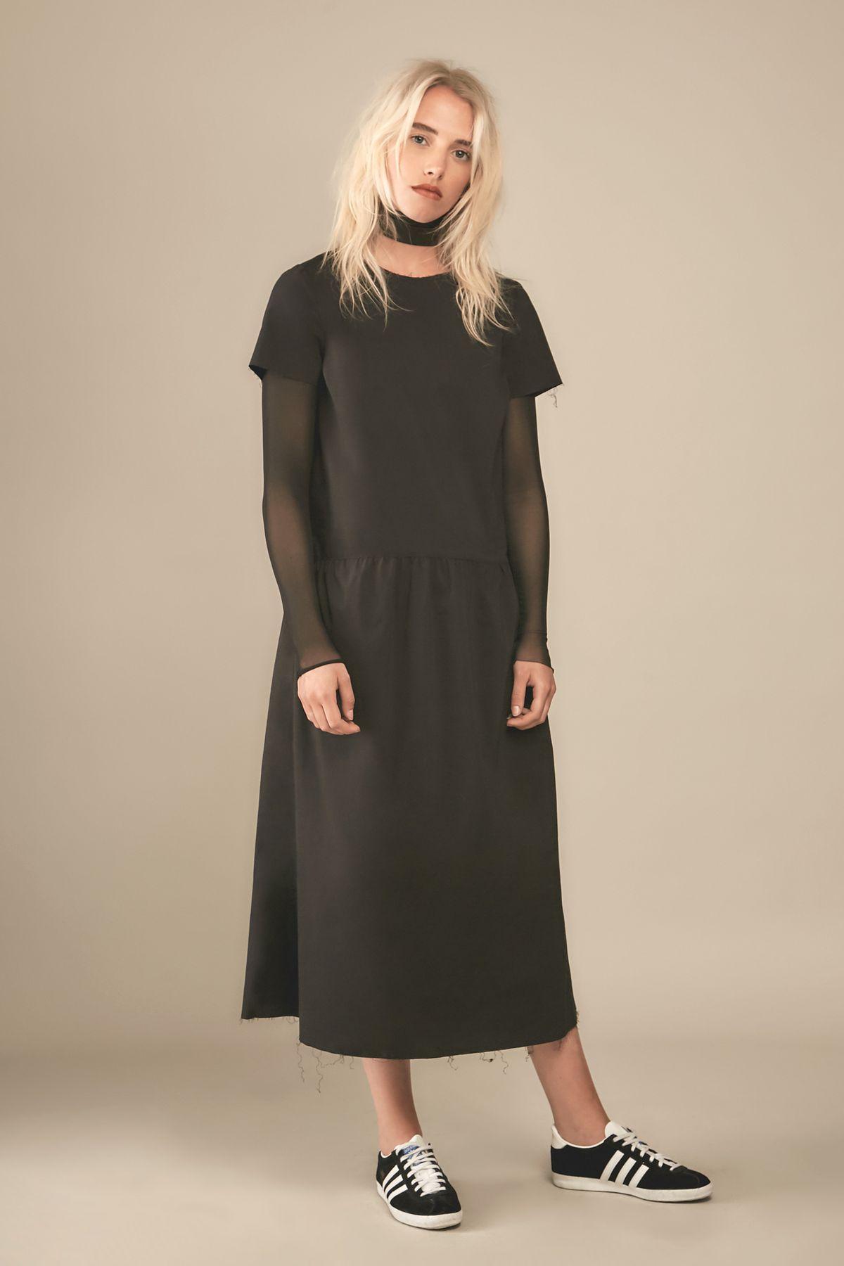 White blonde model wearing oversized black drop-waist dress