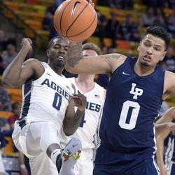 Utah State guard DeAngelo Isby, left, and Life Pacific forward Jonathan Cortez fight for a rebound during an NCAA basketball game Saturday, Dec. 16, 2017, in Logan, Utah. (Eli Lucero/Herald Journal via AP)