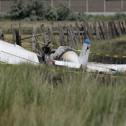 A charred plane sits in a field after it crashed near Legacy Parkway in Centerville on Thursday, June 25, 2020. Bystanders who were traveling on Legacy Parkway pulled two people from the burning plane, who were then transported to the hospital with serious injuries.