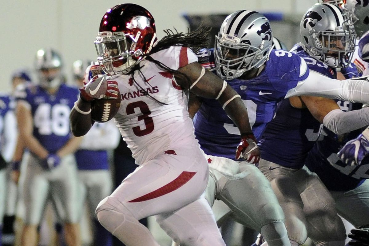 Alex Collins runs away from the K-State defense