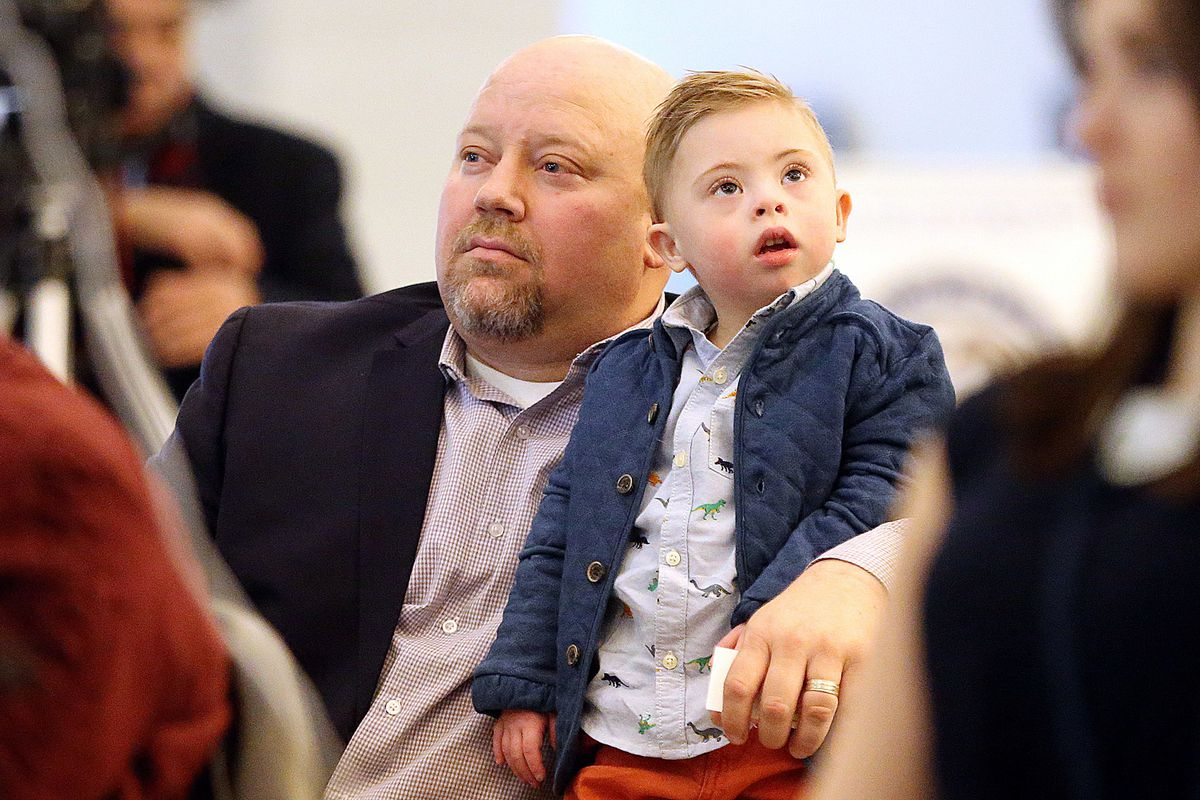 Justin Merkley listens to his wife, Amber, while holding son Finn at the Capitol in Salt Lake City on Monday, Jan. 22, 2018. Rep. Karianne Lisonbee, R-Clearfield, and Sen. Curt Bramble, R-Provo, unveiled a bill that would make it illegal for a medical pro