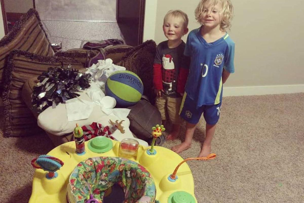 """Arianne Brown's toddler sons Audi and Axel stand proudly in front of their """"fence."""""""