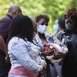 Rashad's mother, Latonja Williams, holds onto her son's football helmet during a memorial for Verner at Urban Prep Academy High School Bronzeville Campus at 521 E 35th St in Ida B. Wells / Darrow Homes Tuesday, Oct. 6, 2020.