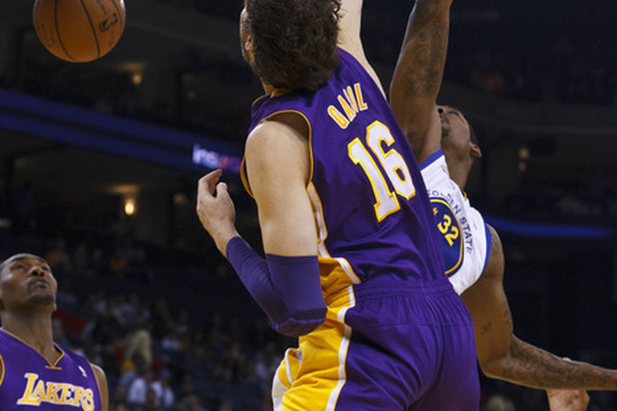Apr 18, 2012; Oakland, CA, USA; Los Angeles Lakers power forward Pau Gasol (16) dunks past Golden State Warriors center Mickell Gladness (32) during the first quarter at Oracle Arena. Mandatory Credit: Jason O. Watson-US PRESSWIRE