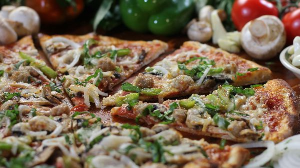 A sliced pizza covered with peppers and onions