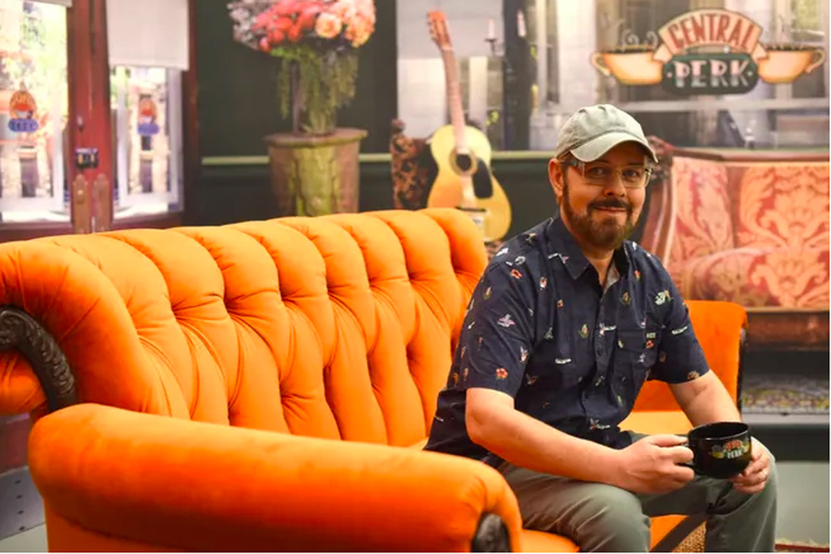 A man in a dark blue button down and olive green baseball cap sits on an orange couch in a coffee shop. He's holding a black mug with both hands.