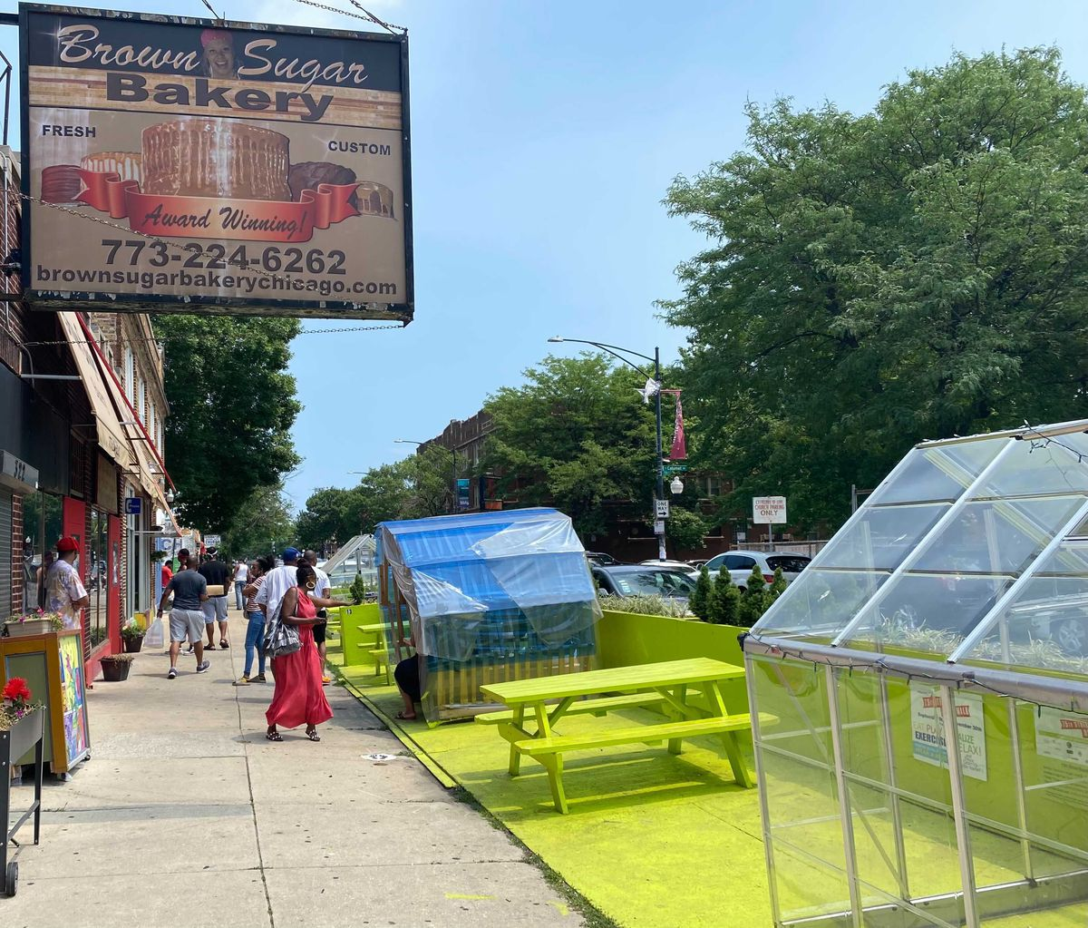 Shoppers walk along the street Saturday afternoon in the 300 block of East 75th Street in the area's lively business district, which includes Brown Sugar Bakery.