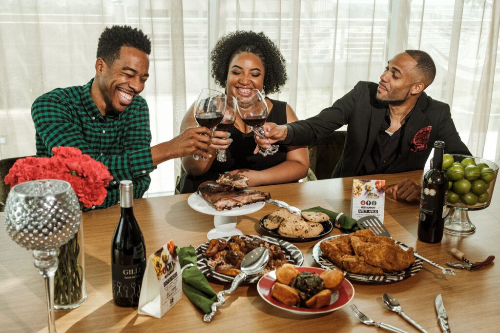 Black restaurant week founders Derek Robinson, Falayn Ferrell, and Warren Luckett laugh and cheers each other with wine at table full of food
