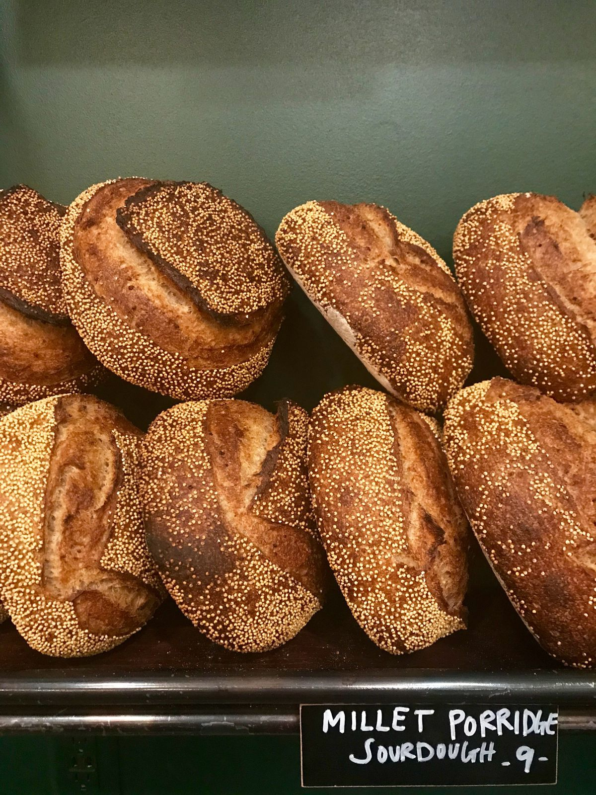 Two rows of millet porridge sourdough loaves at Evergreen Butcher and Baker in Kirkwood Atlanta