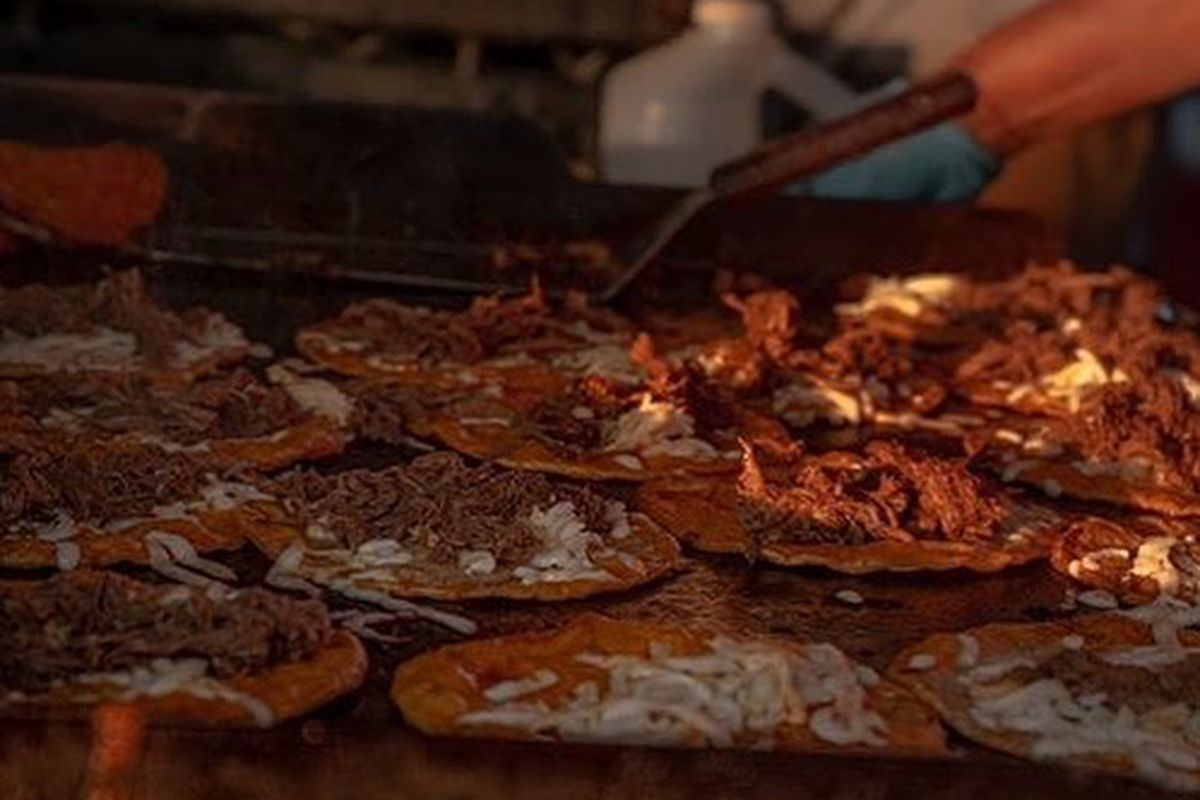 Open-faced birria tacos topped with beef birria and cheese cooking atop a griddle at Chef Smokeys ATL in Austell, GA