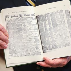 """Elder M. Russell Ballard, of the Quorum of the Twelve Apostles of The Church of Jesus Christ of Latter-day Saints, shows an image of The Newbury Weekly News in a copy of the book """"Crusader for Righteousness"""" by his grandfather, Melvin J. Ballard, while speaking to reporters from the LDS Church News in his office at the Church Administration Building in Salt Lake City on Friday, June 30, 2017."""