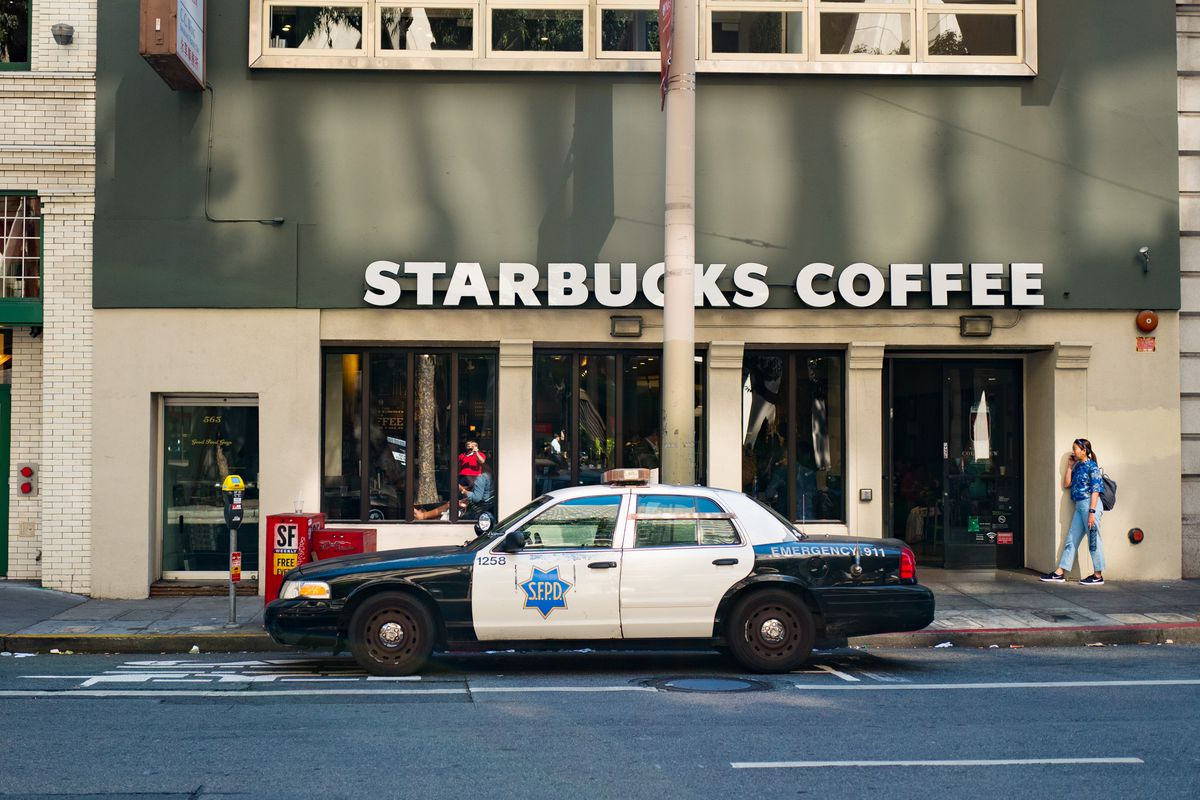 A police car parked in front of a Starbucks.