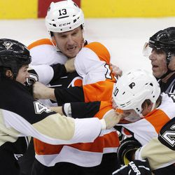 CORRECTS PENGUINS PLAYER NAME TO ARRON, NOT AARON - Philadelphia Flyers' Pavel Kubina (13) and Brayden Schenn (10) both tangle with Pittsburgh Penguins' Arron Asham, left, during a third-period fight, as linesmen Brad Lazarowich (86) tries to separate them in the final minute of an NHL hockey game in Pittsburgh Sunday, April 1, 2012. The Flyers won 6-4.