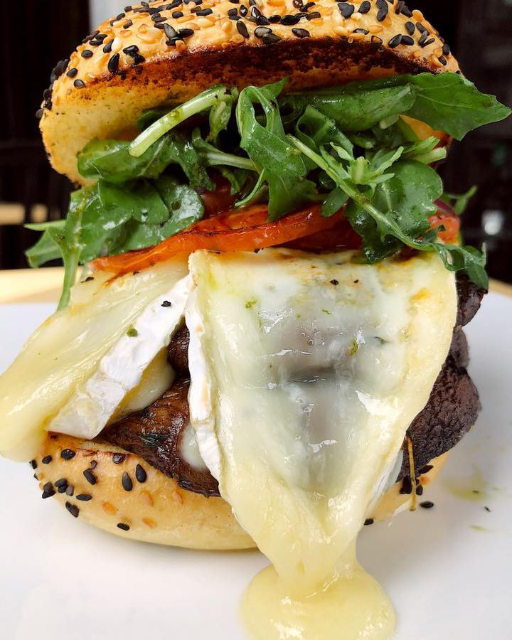 A very tall mushroom burger with oozing cheese.