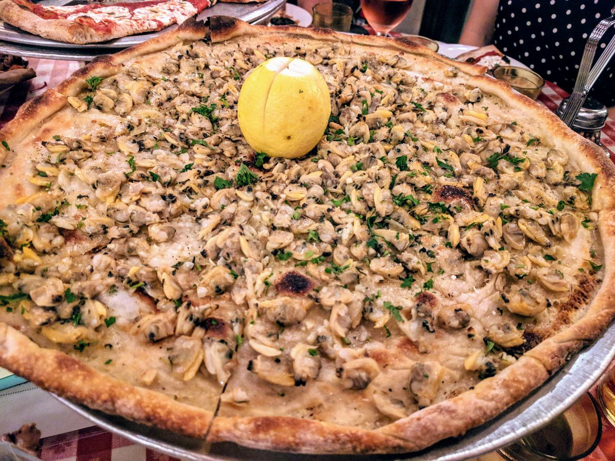 A pizza covered with deshelled bivalves with a whole lemon standing up in the middle, skin on.