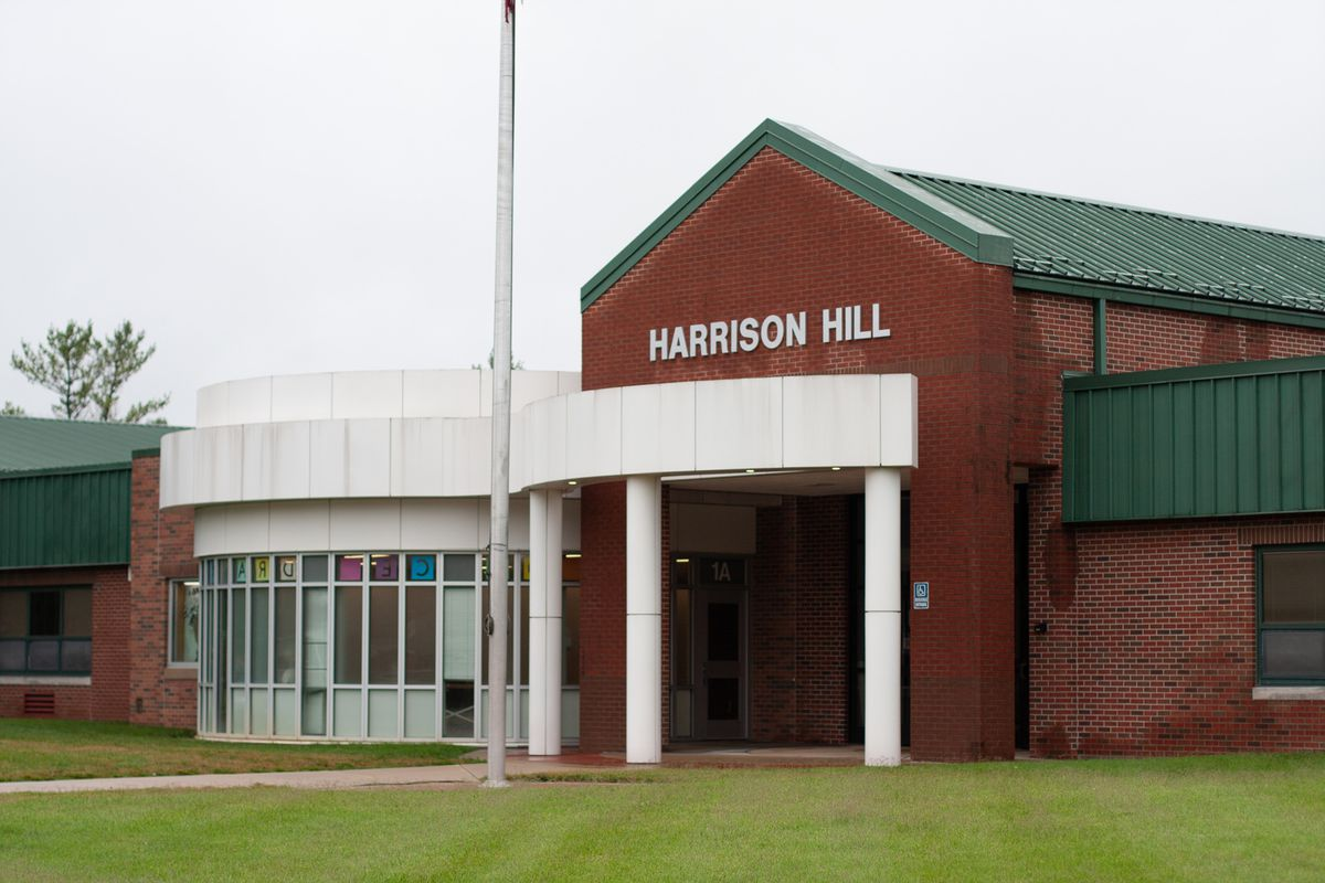 The facade of Harrison Hill Elementary School, a red brick building with a green roof.