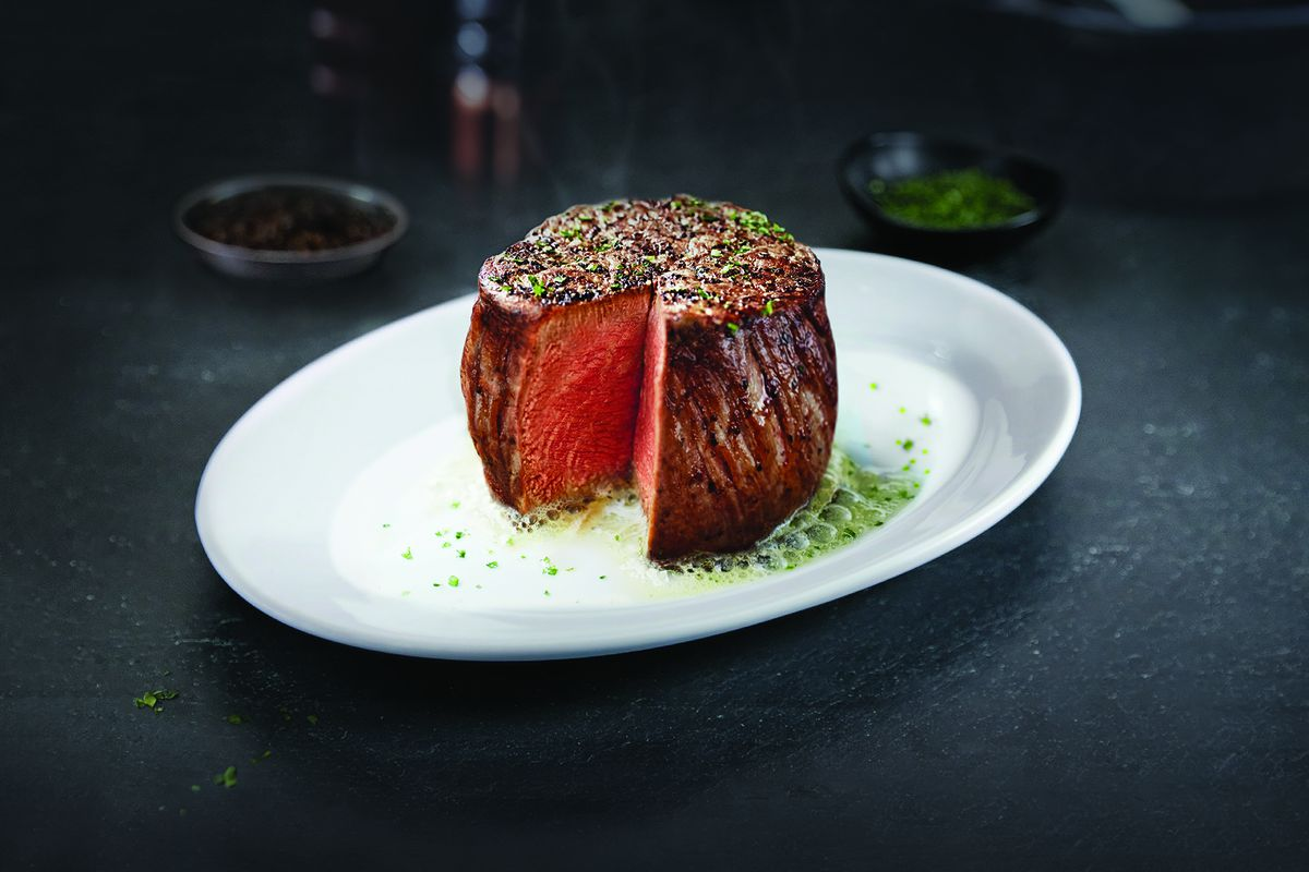 A thick filet of steak sits on a white plate, cut open to reveal a pink center