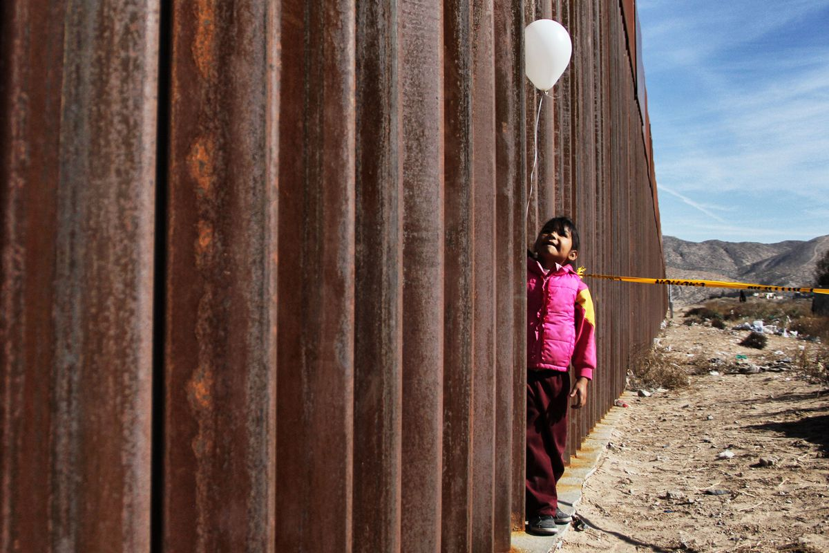 A child at the US-Mexico border wall.