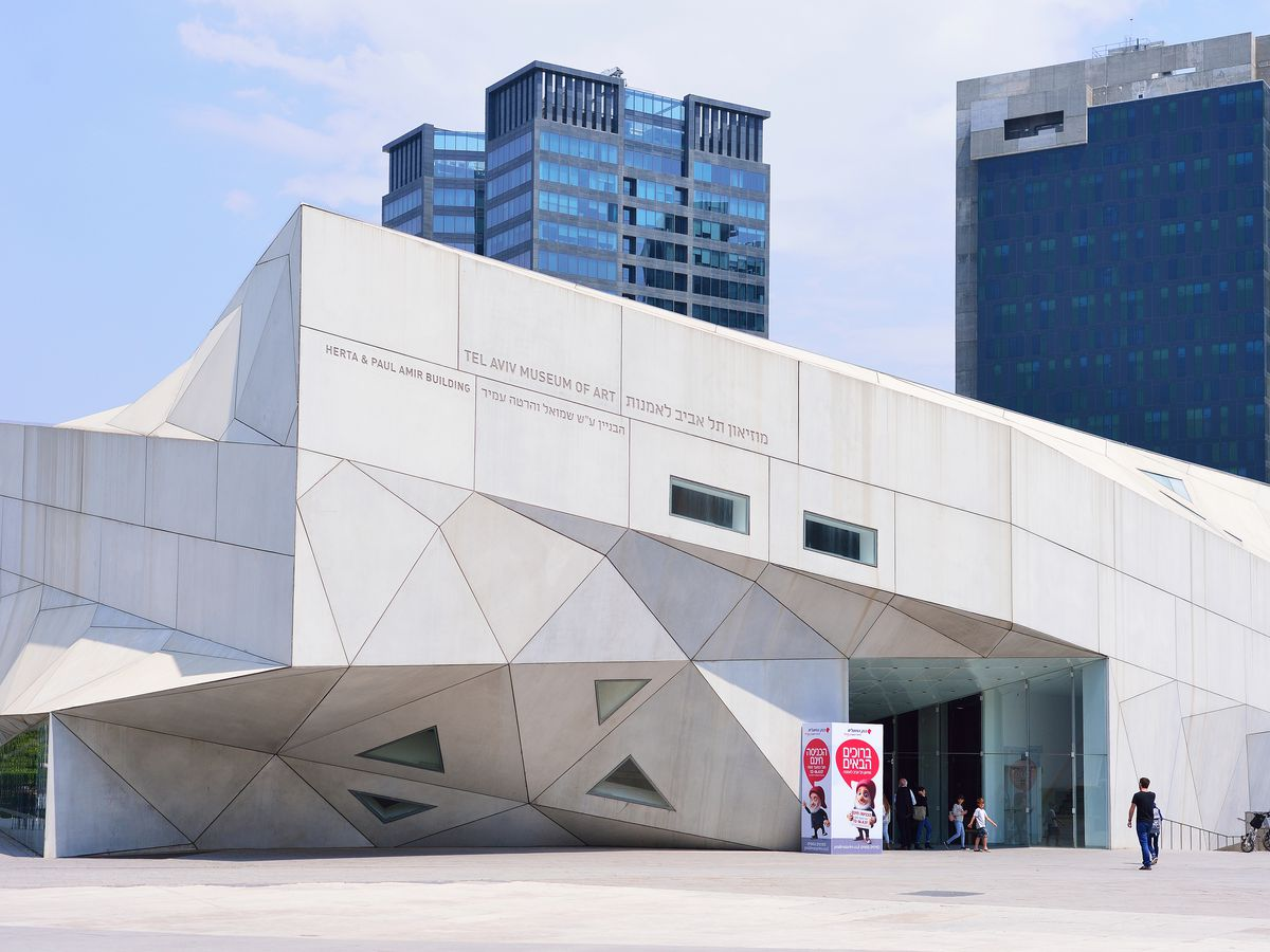The exterior of the Tel Aviv Museum of Art. The facade is white with a geometric structure.
