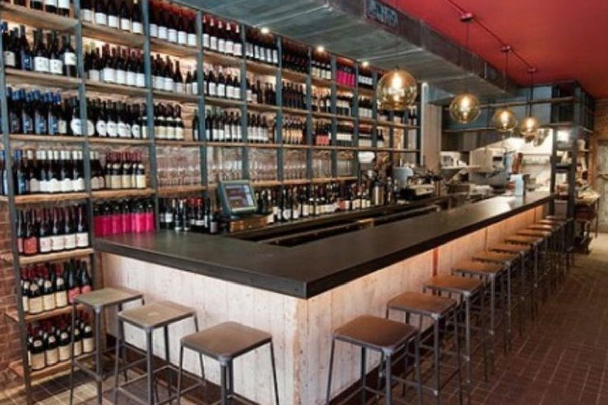 The bar at Terroir Tribeca, with wine bottles lining the wall behind it