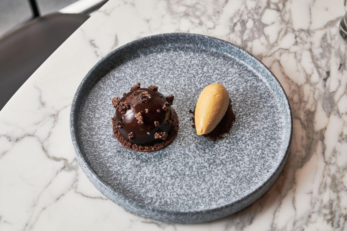 Circular milk chocolate tiramisu with ice cream on a grey plate