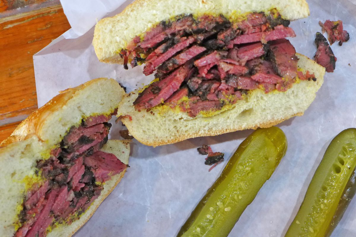 A red meat sandwich with a pair of pickles.