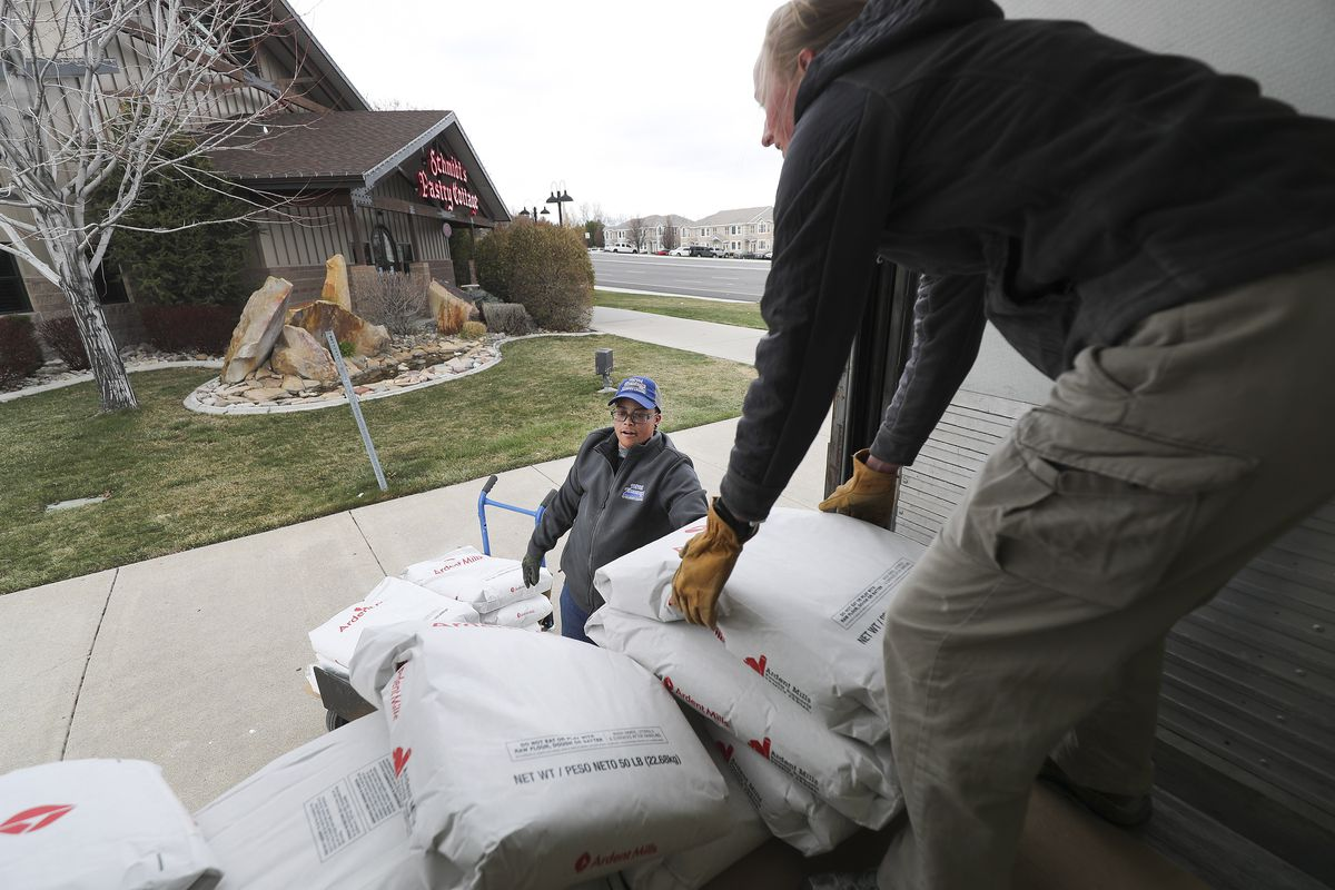 Reece Norbrey and Bonnie Dienslake unload 2,500 pounds of flour at Schmidt's Pastry Cottage in South Jordan on Tuesday, March 24, 2020. Ardent Mills donated the flour for the bakery's free bread project, where customer are given two loaves of bread — one for them and one to share during the coronavirus pandemic.