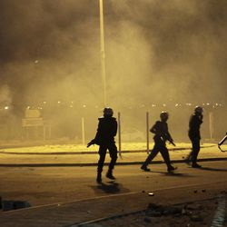 """Riot police fire tear gas and stun grenades to disperse villagers gathering near the site in Sadad, Bahrain, early Saturday, Sept. 29, 2012, where a youth was killed during an anti-government protest, allegedly by police shotgun fire. An Interior Ministry statement said a police patrol was attacked with petrol bombs and iron rods late Friday, and one person died when """"policemen defended themselves."""" A witness among protesters said demonstrators were marching against the government when a policeman suddenly stepped out near the youth and shot him at close range."""