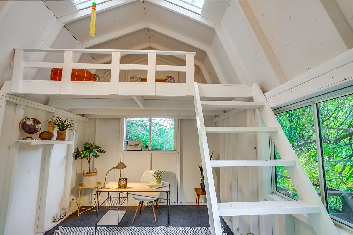 A white barn-like interior with an office setup and a ladder up to a small loft.
