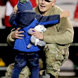 Airman Gregory Slattery greets his son during a surprise reunion at the Iowa-UW game.