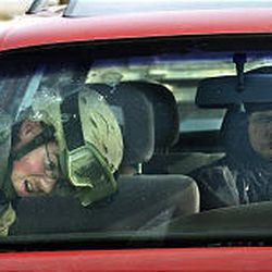 An Iraqi woman sits in her car while a U.S. soldier searches it at a highway checkpoint near Ramadi. The car resembled one sought in connection with a sniper.