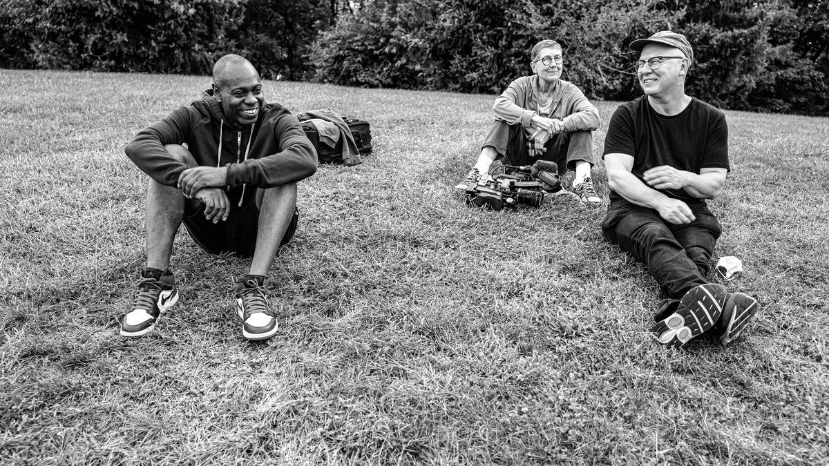 A black-and-white photo of three people sitting on grass together and smiling.