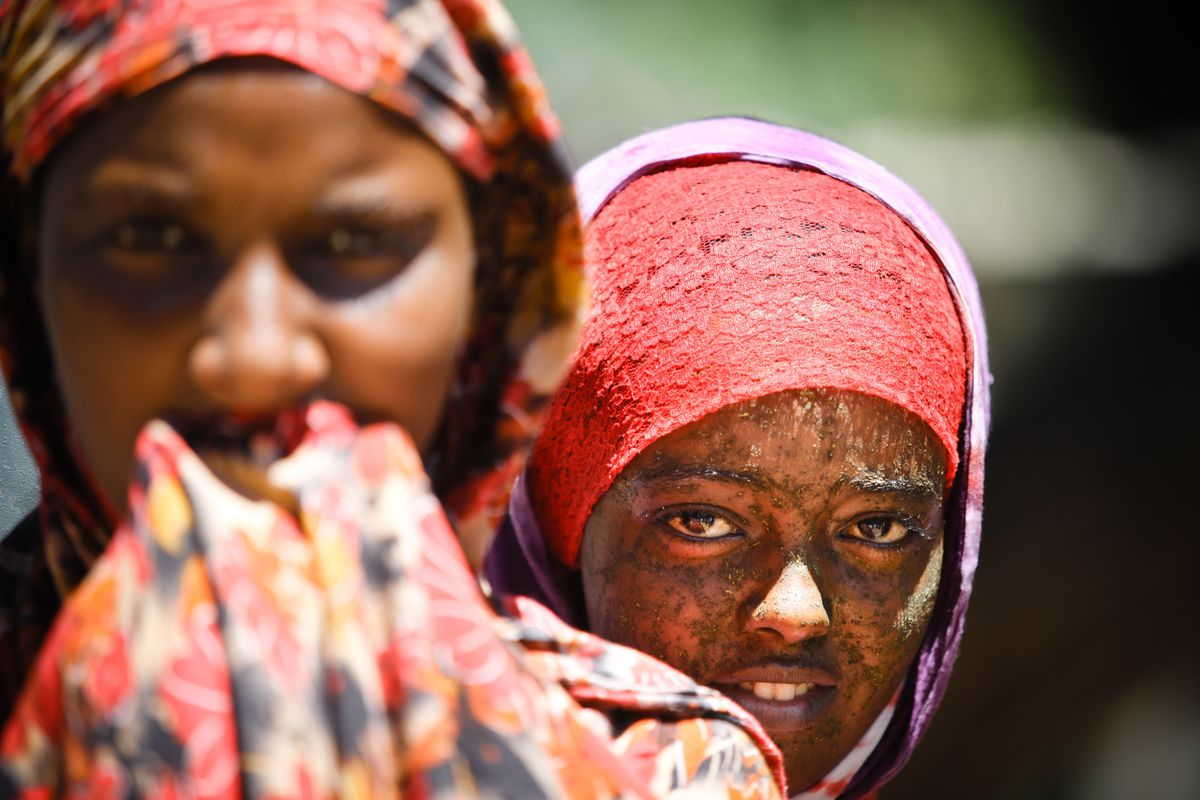A young Somali girl hides behind her sister while soldiers patrol the village of Jamuhuria near the frontline on February 20, 2012 in Mogadishu, Somalia.