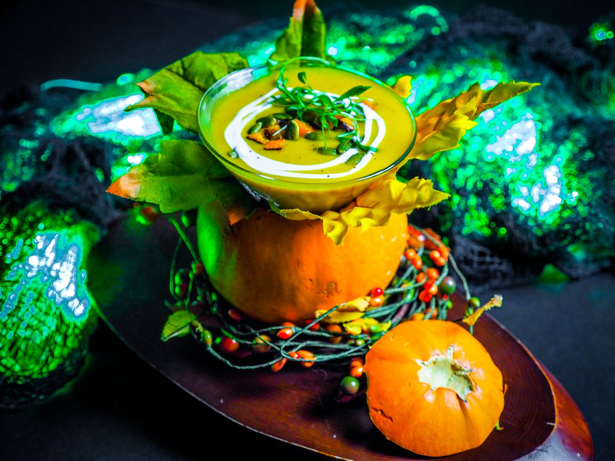 A glass of soup inside a small pumpkin