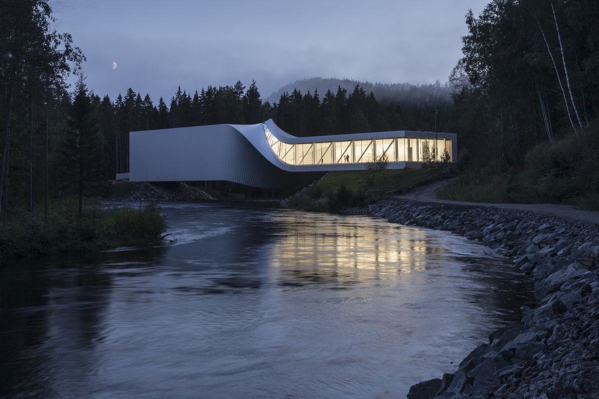 A twisting white bridge with glass walls spanning a river.