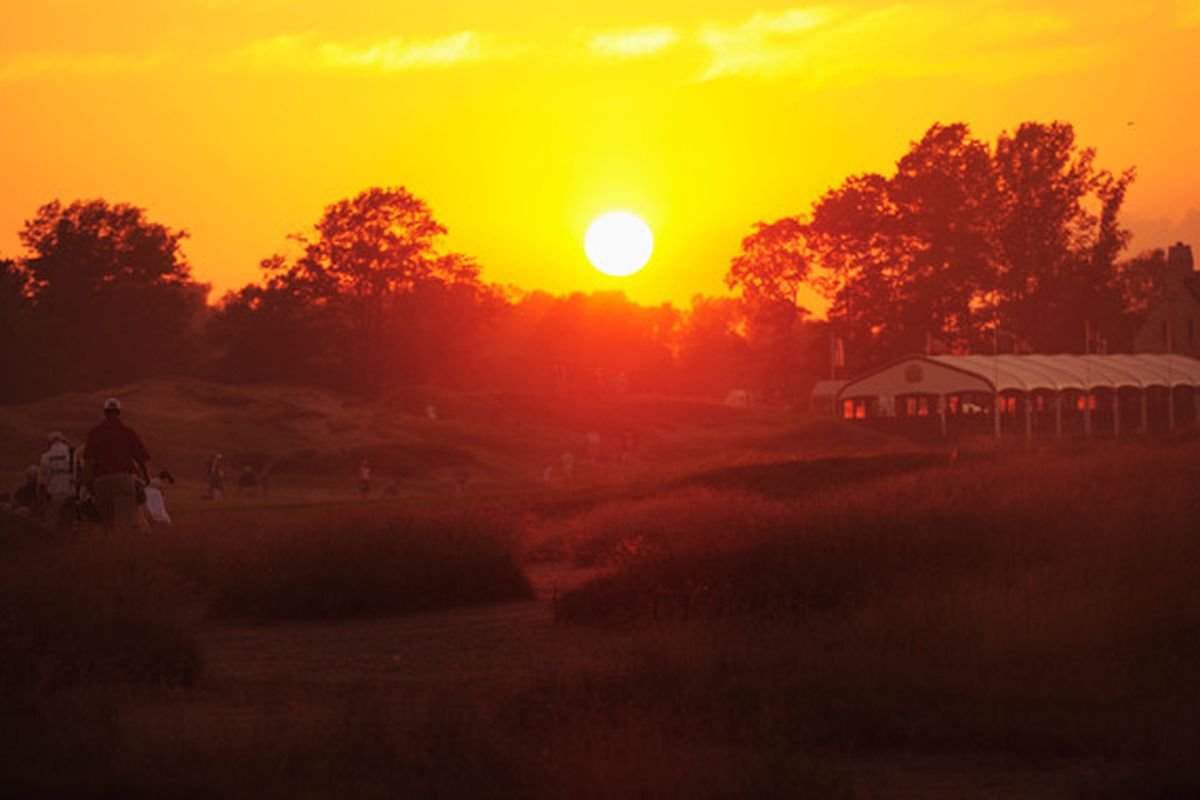 KOHLER WI - AUGUST 12:  The sun sets as golfers walk the ninth hole during the first round of the 92nd PGA Championship on the Straits Course at Whistling Straits on August 12 2010 in Kohler Wisconsin.  (Photo by Stuart Franklin/Getty Images)