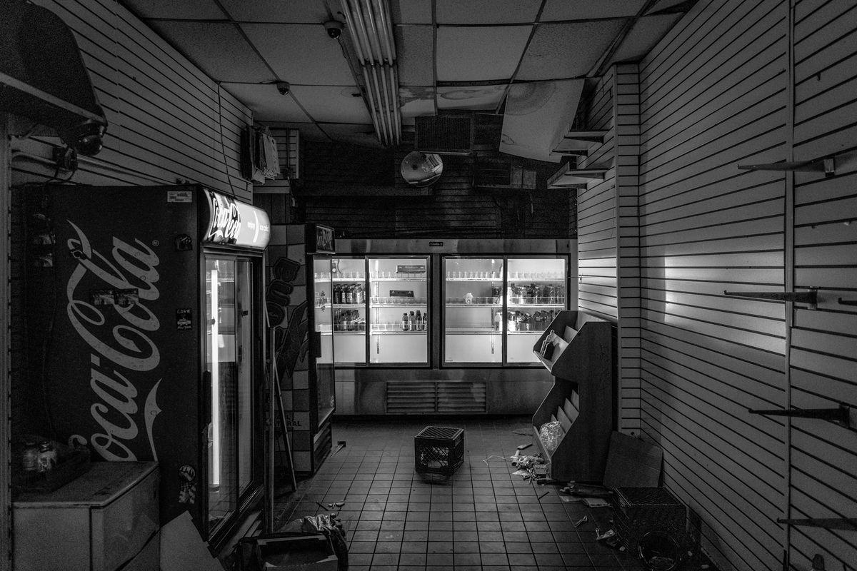 Gem Spa mit ausgeschaltetem Licht, das von meist leeren Getränkekühlern beleuchtet wird