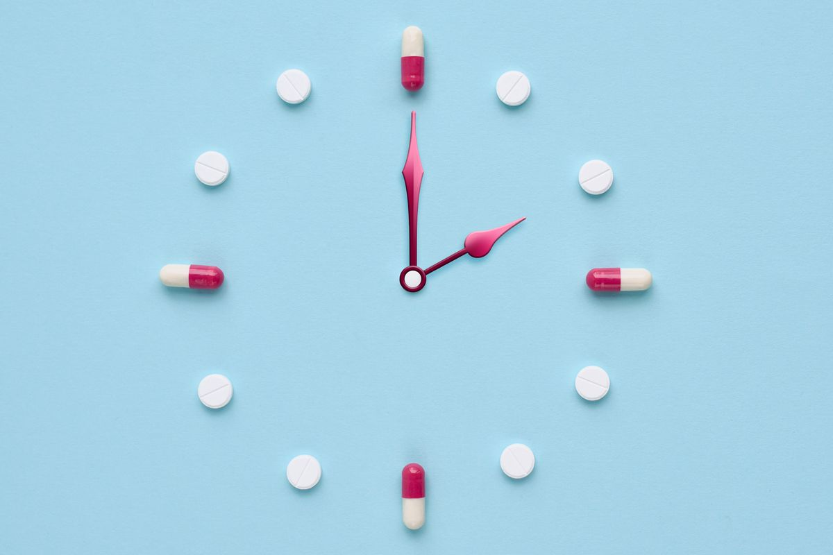 A clock face with pill capsules at the three, six, nine, and twelve.