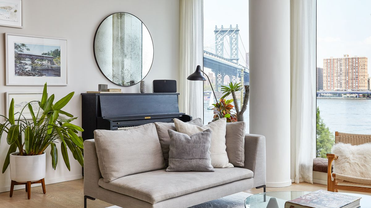 A living area with a couch, arm chair, upright piano, planter with a plant, and a table. There are floor to ceiling windows overlooking the New York City waterfront and a bridge. There is a mirror and works of art on the wall.